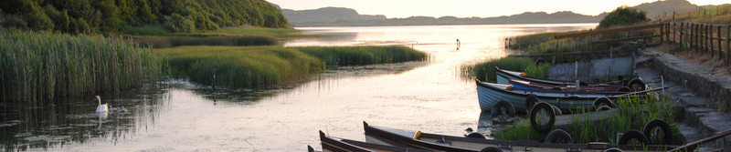 Rowing boats moored at the side of the new lake on a warm summer's evening