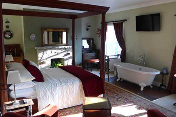 a large room with four poster bed and rolltop bath
